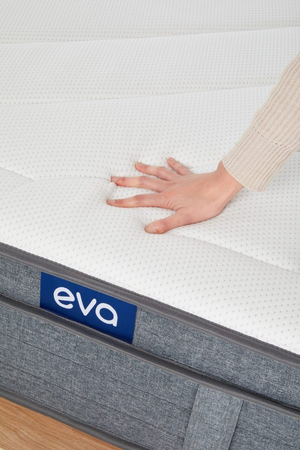 close up of person placing hand on eva mattress