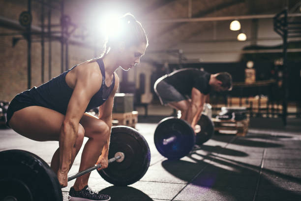 man and woman performing deadlifts at a gym