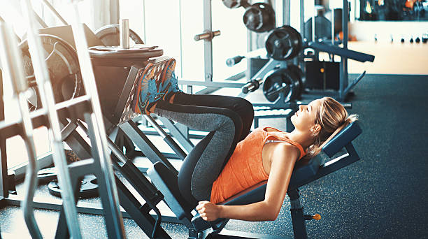 woman performing leg press exercise at the gym - an exercise to avoid if you have back pain