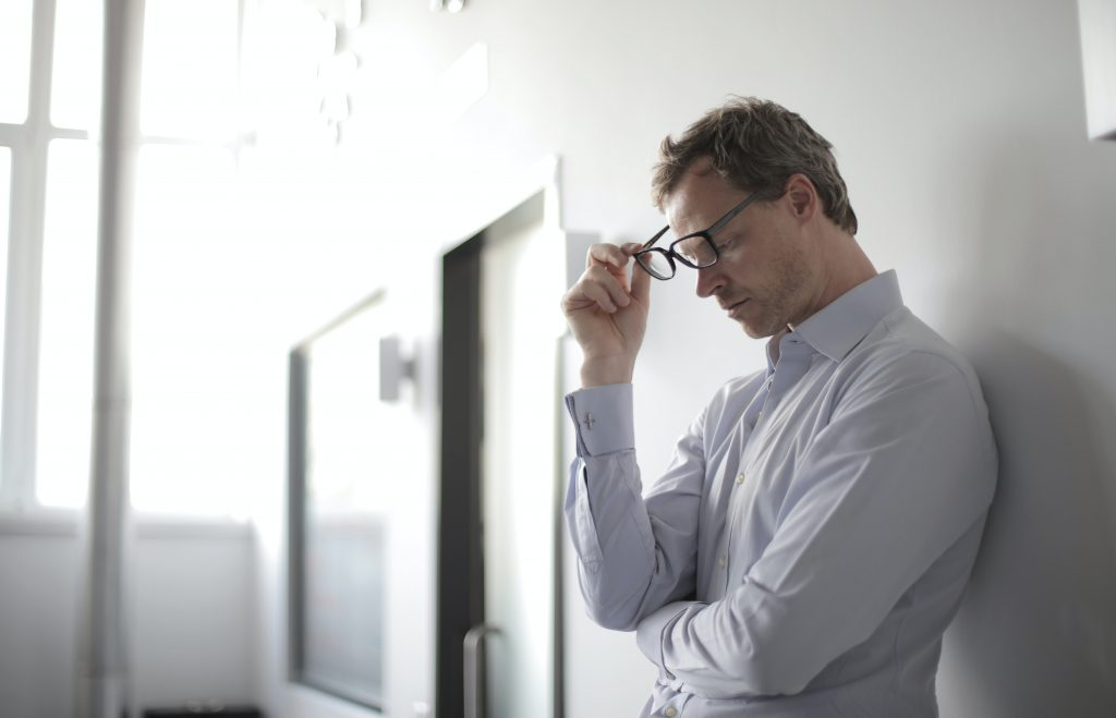 Stressed male office worker standing against wall with glasses partially removed
