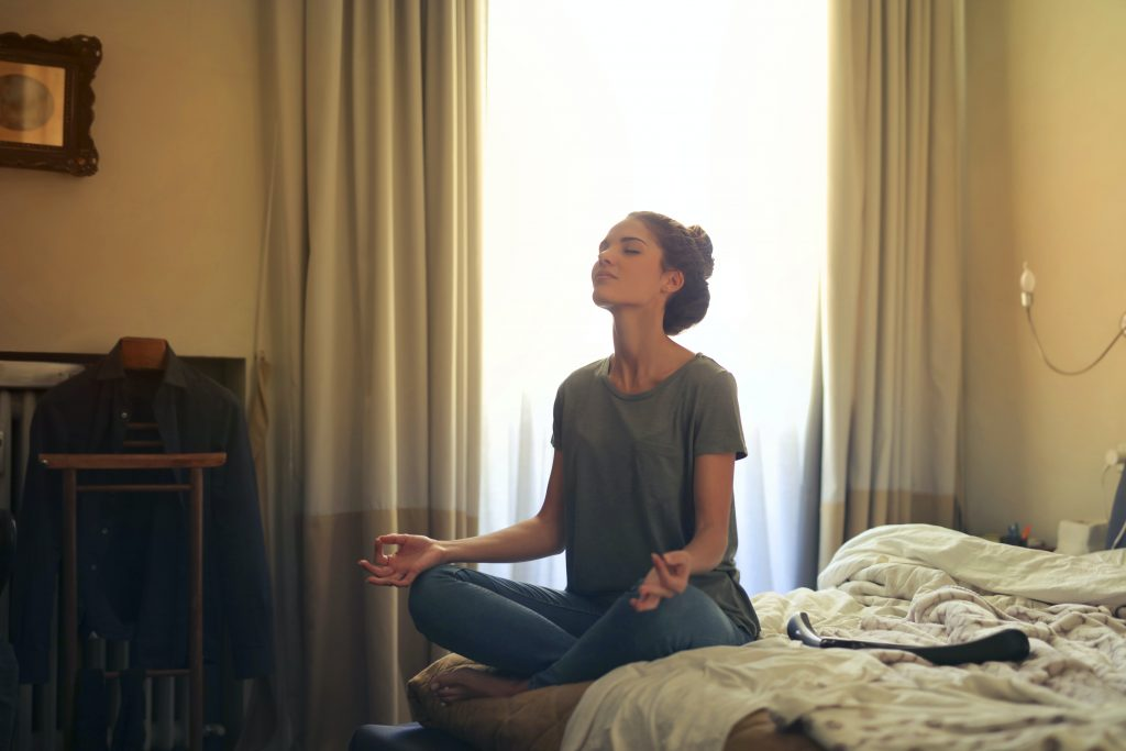woman sitting on a bed meditating