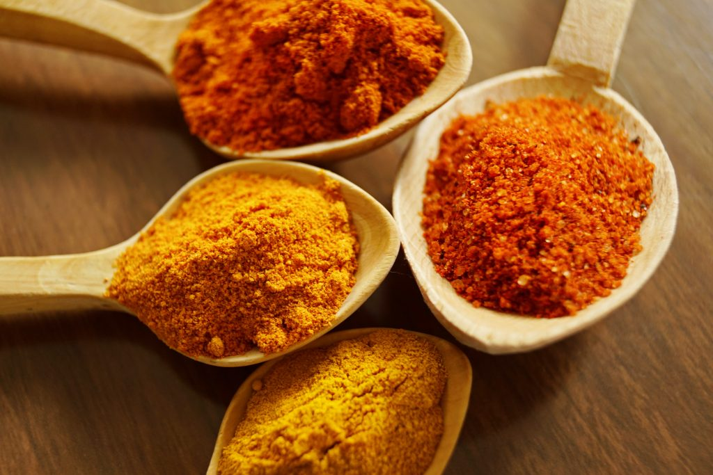 wooden teaspoons filled with tumeric, ginger and other anti inflammatory spices