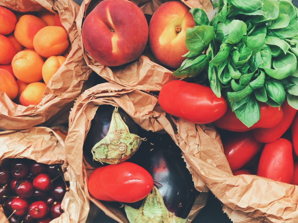 Overhead view of fruits and vegetables in paper bags