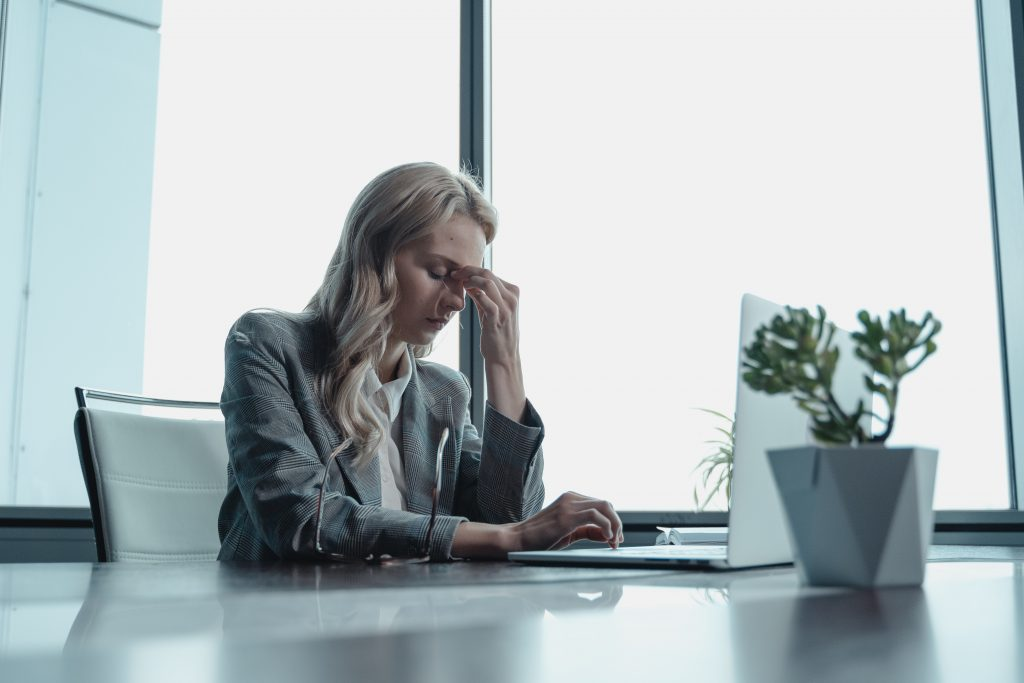 Stressed female office worker, sitting at desk with hand pressed against forehead