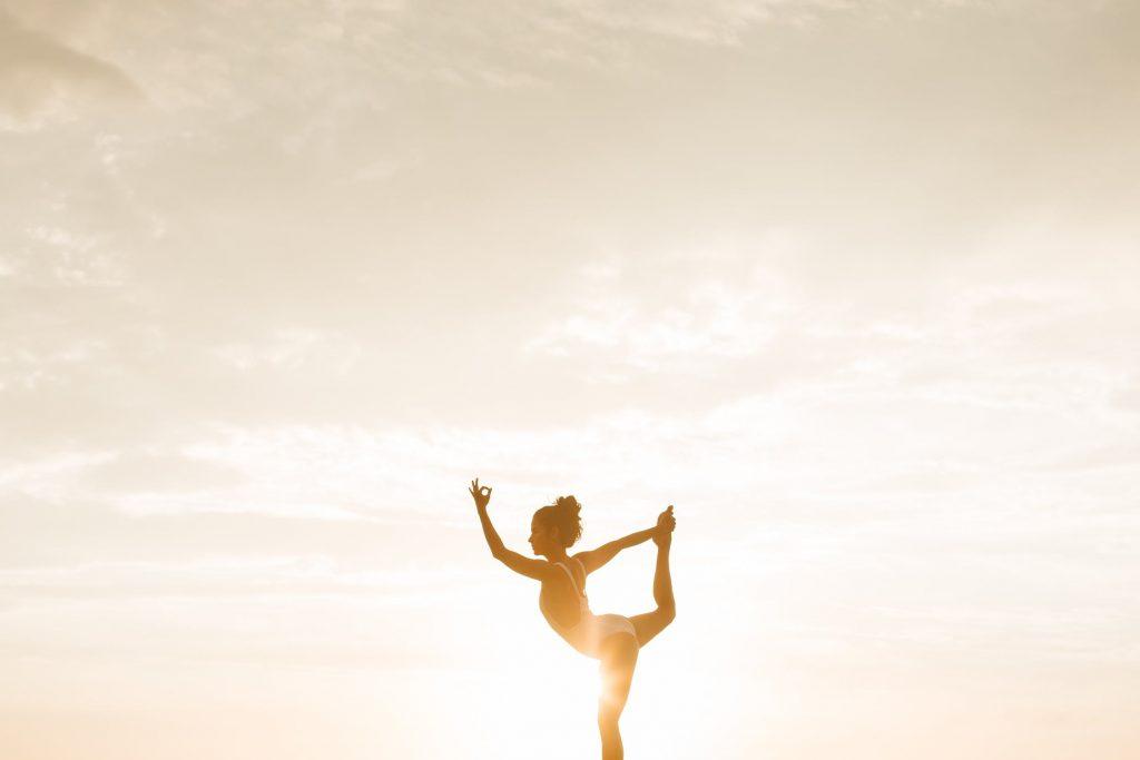 woman holding yoga pose during sunset