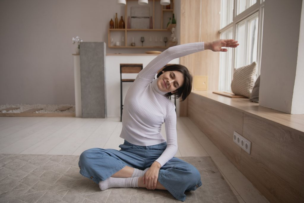 woman sitting on floor stretching with smile on face