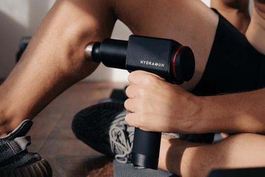 man using hydragun massage gun
