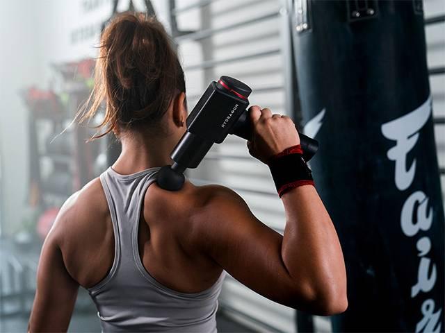 woman at gym using hydragun massage gun