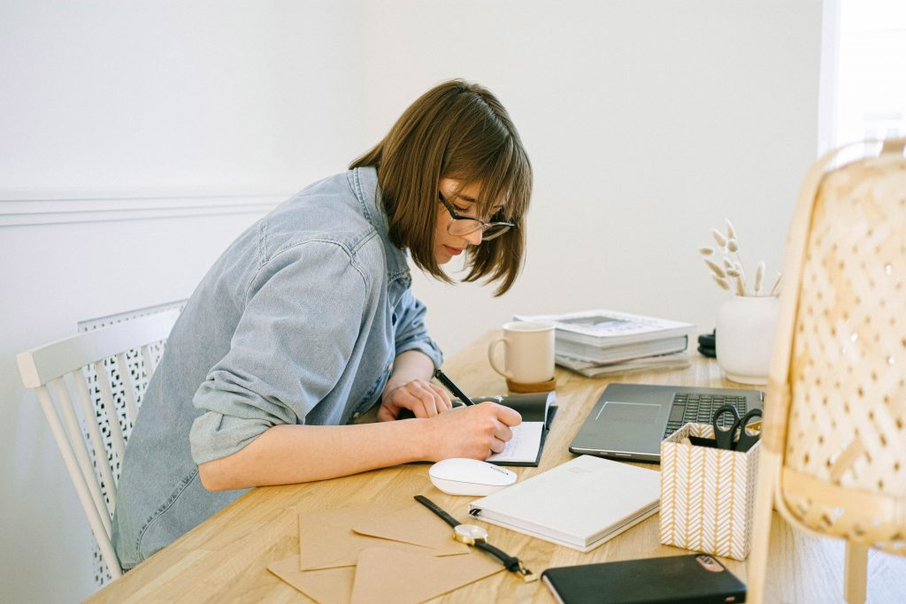 woman sitting at desk, slouching over her work