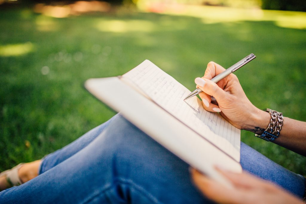 woman sitting on grass writing in journal