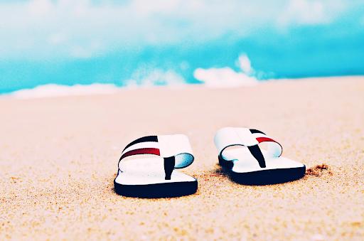 close up image of flip flops on sand