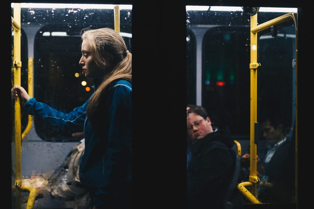woman standing on bus commuting