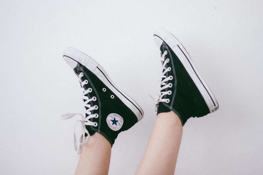image of a person wearing high top black converse shoes