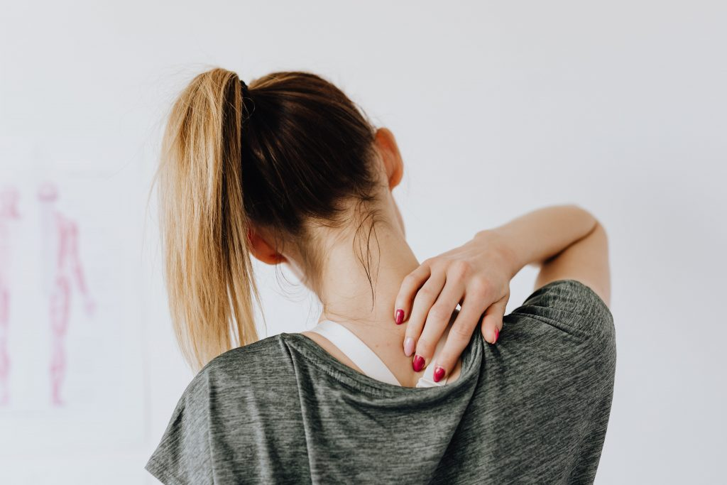Woman reaching hand to a spot that is causing discomfort in upper back