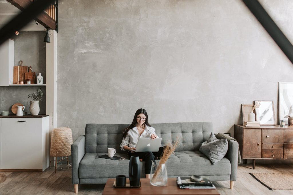 Woman sitting on a lounge looking down at a laptop on her lap
