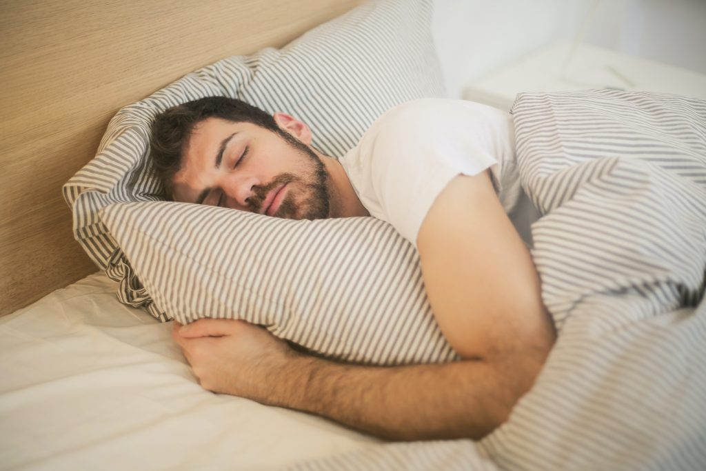man sleeping in bed side position