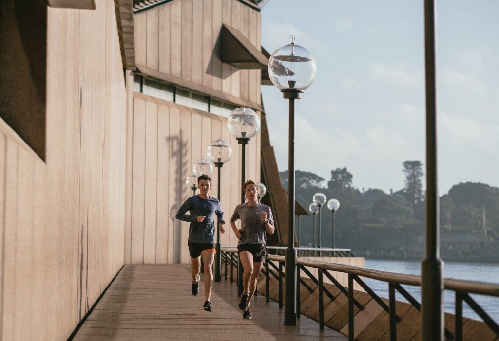 man and woman running along waterfront