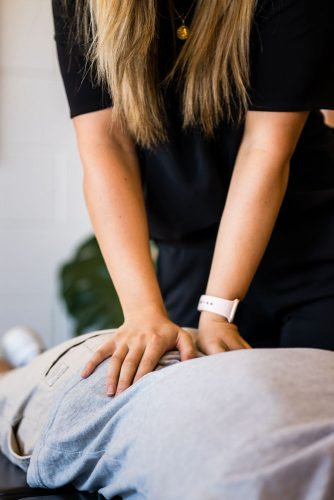 Frankston Heights Chiropractor performing lower back adjustment on patient