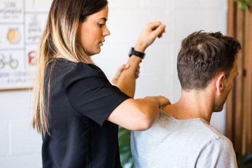 Hillside Chiropractor performing shoulder assessment on patient
