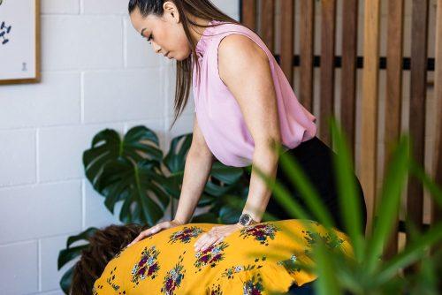 Merricks North Chiropractor performing back adjustment on female patient