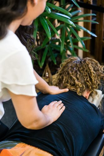 Safety Beach Chiropractor performing back adjustment on female patient
