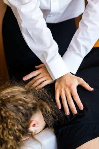 Seaford Chiropractor performing upper back adjustment on female patient