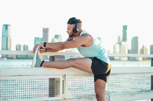 man stretching hamstring and calves while taking a break from a run