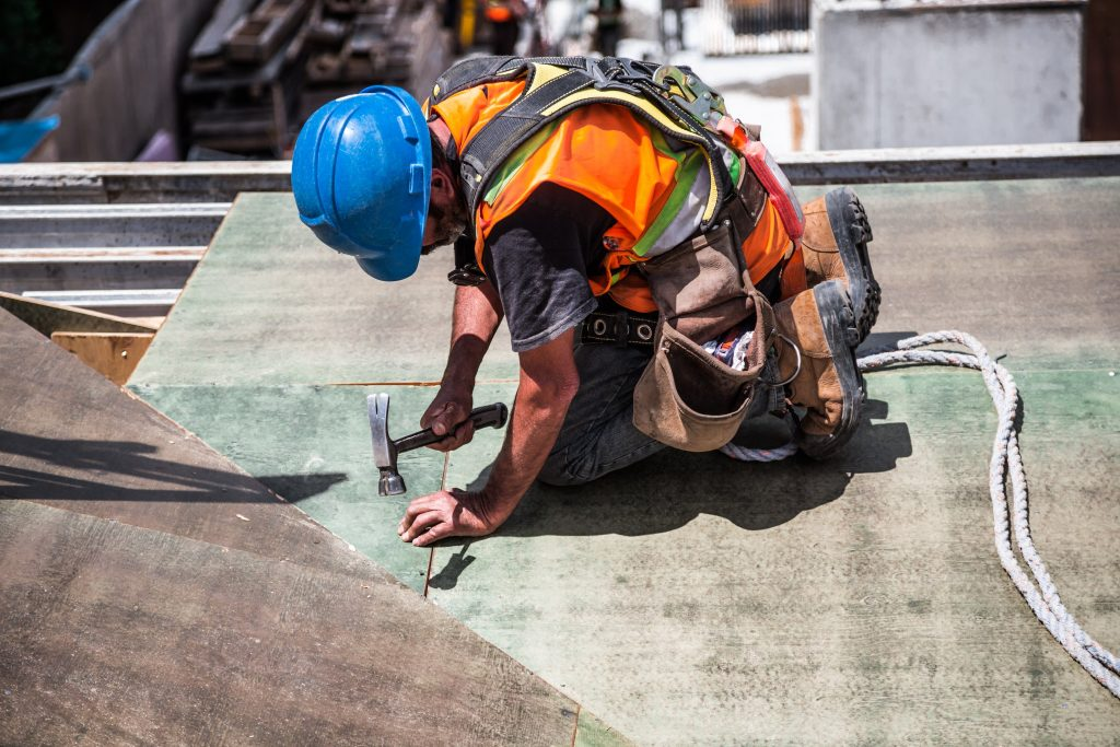 construction worker bent on knees hammering a nail into a surface