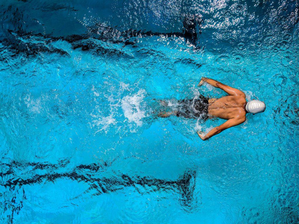 male swimming breastroke laps in pool
