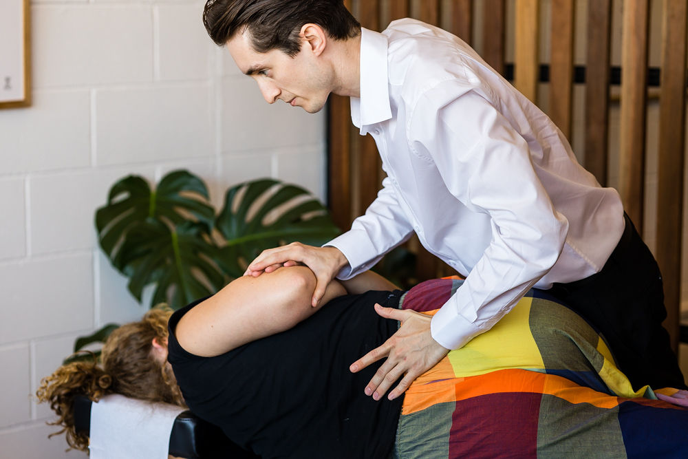 Chiropractor performing adjustment on female patient