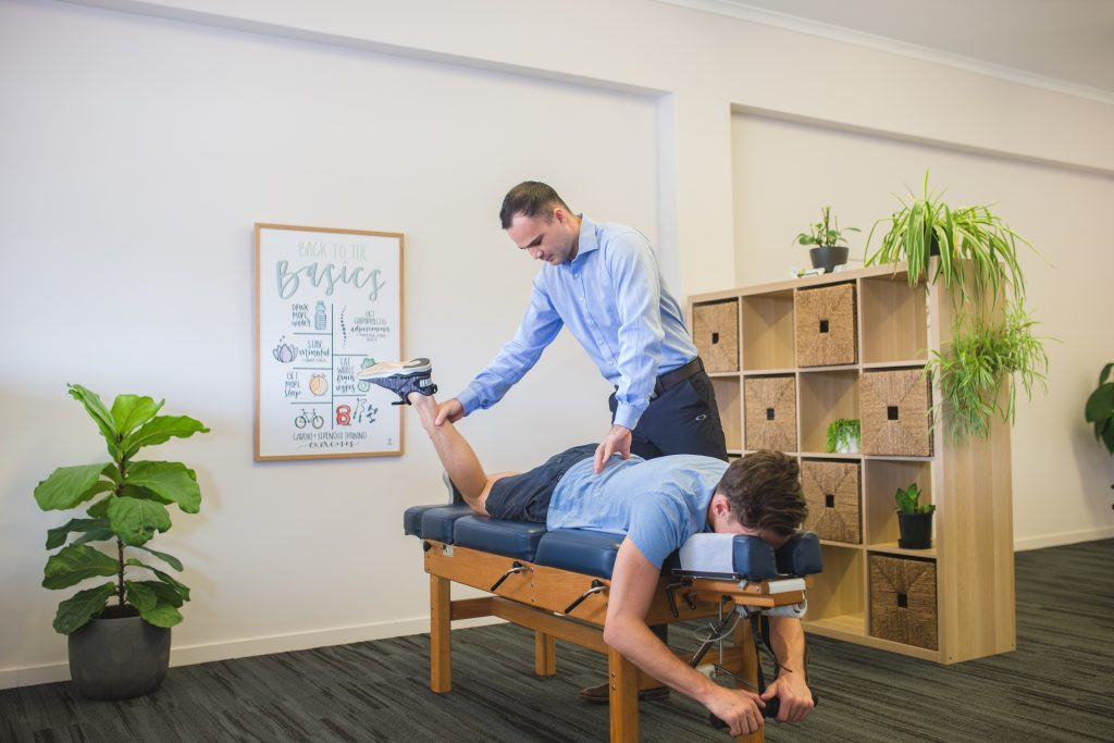 Kawana Chiropractor performing leg assessment on male patient