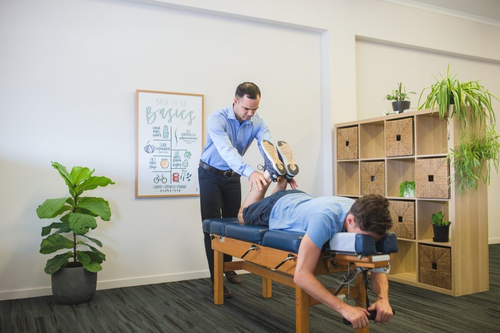 West Rockhampton Chiropractor performing leg length assessment on male patient