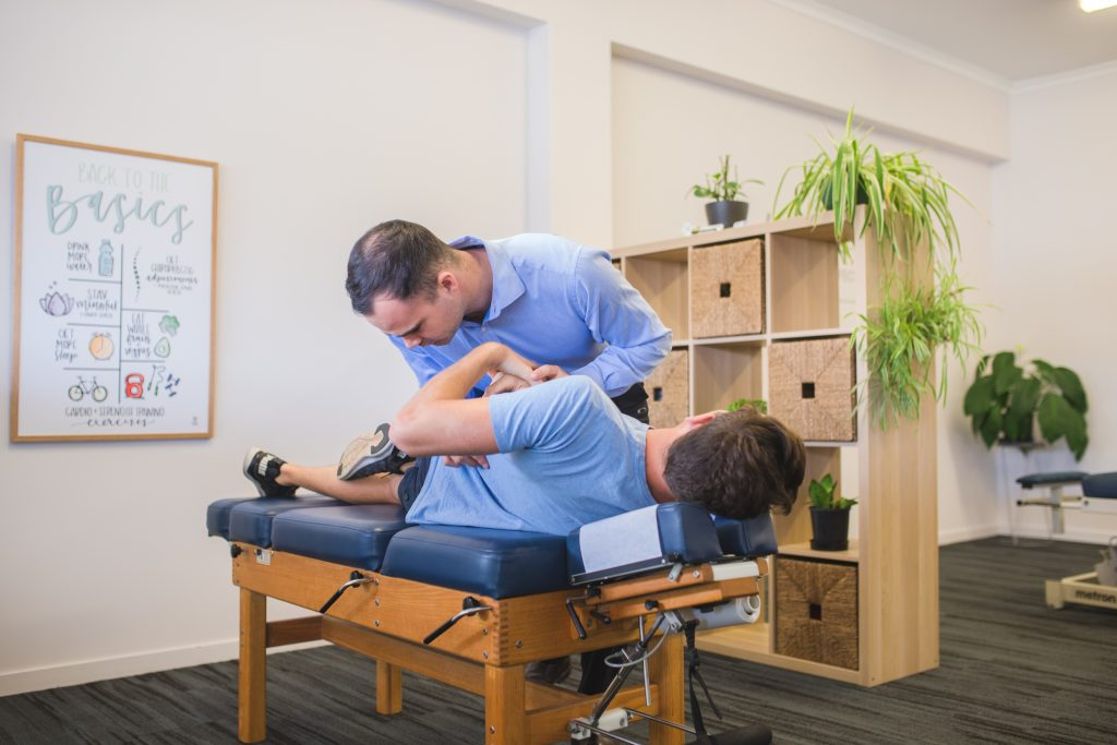 Rockhampton City Chiropractor performing back adjustment on male patient