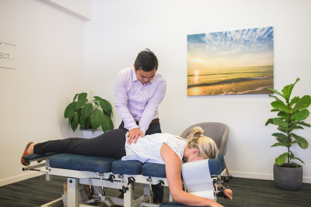 Lakes Creek Chiropractor performing lower back adjustment on female patient
