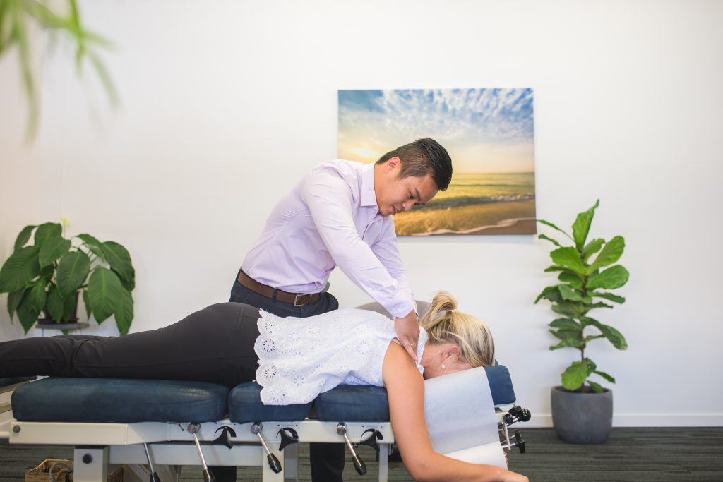 Frenchville Chiropractor performing upper back adjustment on female patient