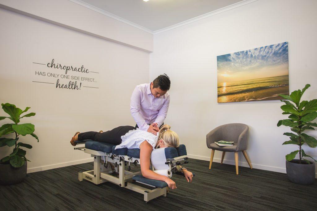Rockhampton Chiropractor performing upper back adjustment on female patient