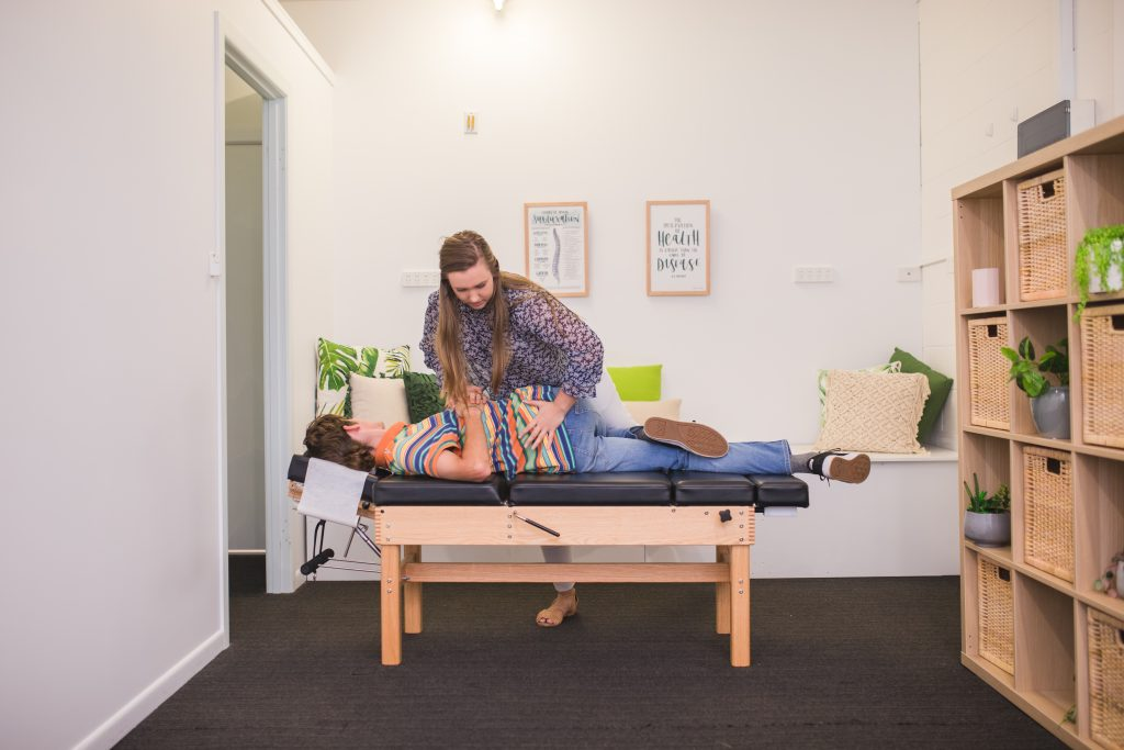 Dr. Jessie (Yeppoon Chiropractor), performing back adjustment on male patient