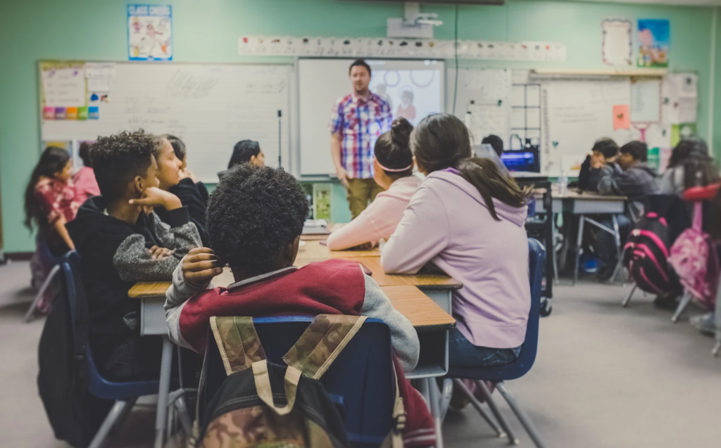 Teacher standing in front of class of seated students in classroom