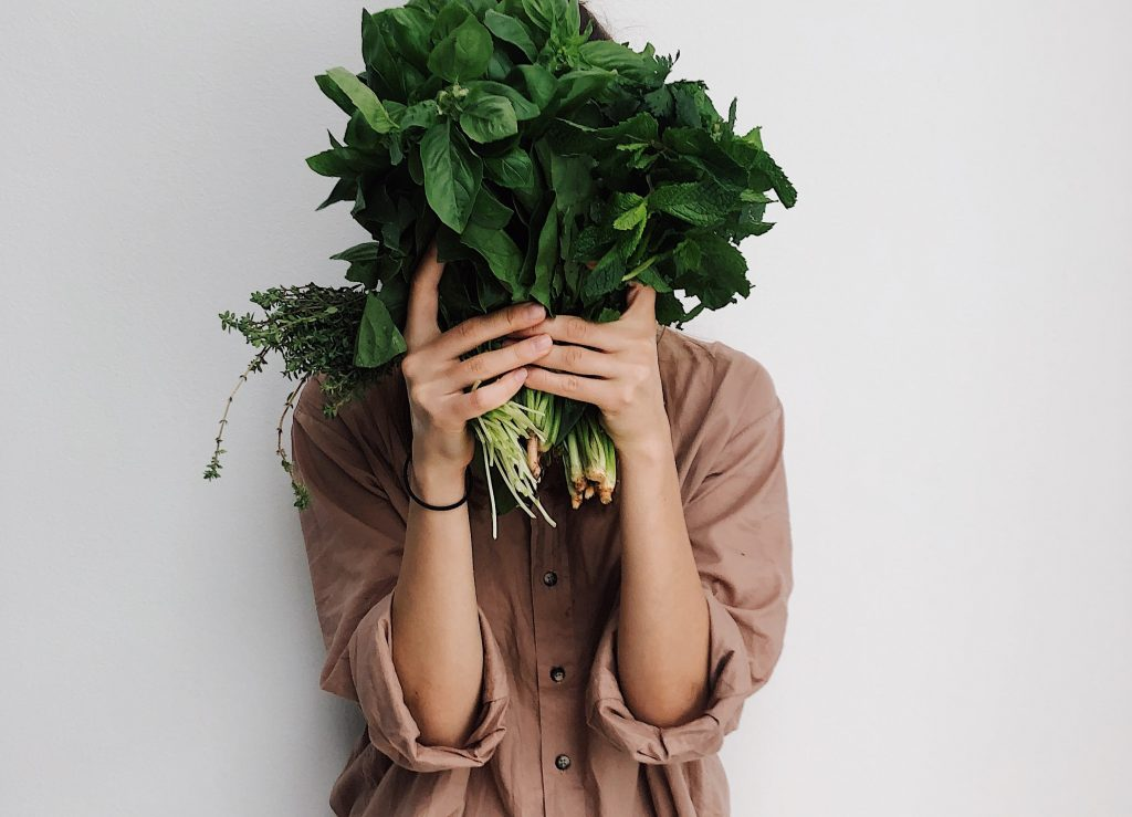 Woman holding bunch of green vegetables in front of face