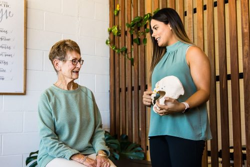 Chiropractor consulting with elderly female patient using pelvic prop