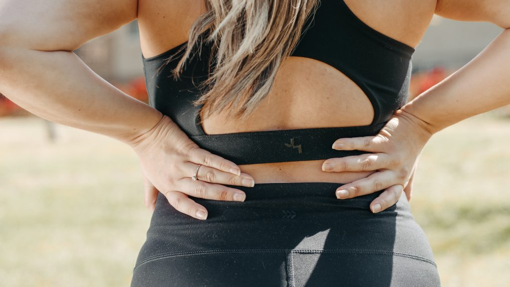 Close up image of female in activewear with hands on lower back