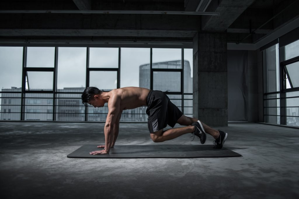man performing mountain climbers on yoga mat in empty building space