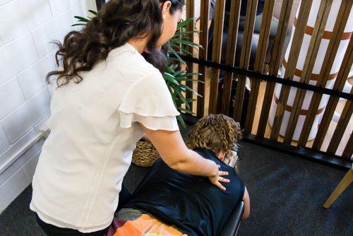 breamlea chiropractor performing upper back adjustment on patient