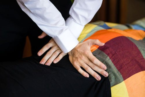 Close up image of bells beach chiropractor performing lower back adjustment on female patient