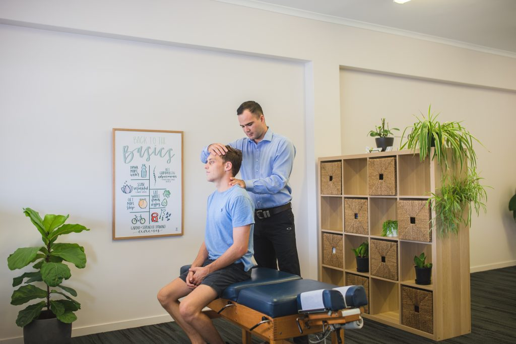 Upper Coomera Chiropractor performing neck assessment on male patient