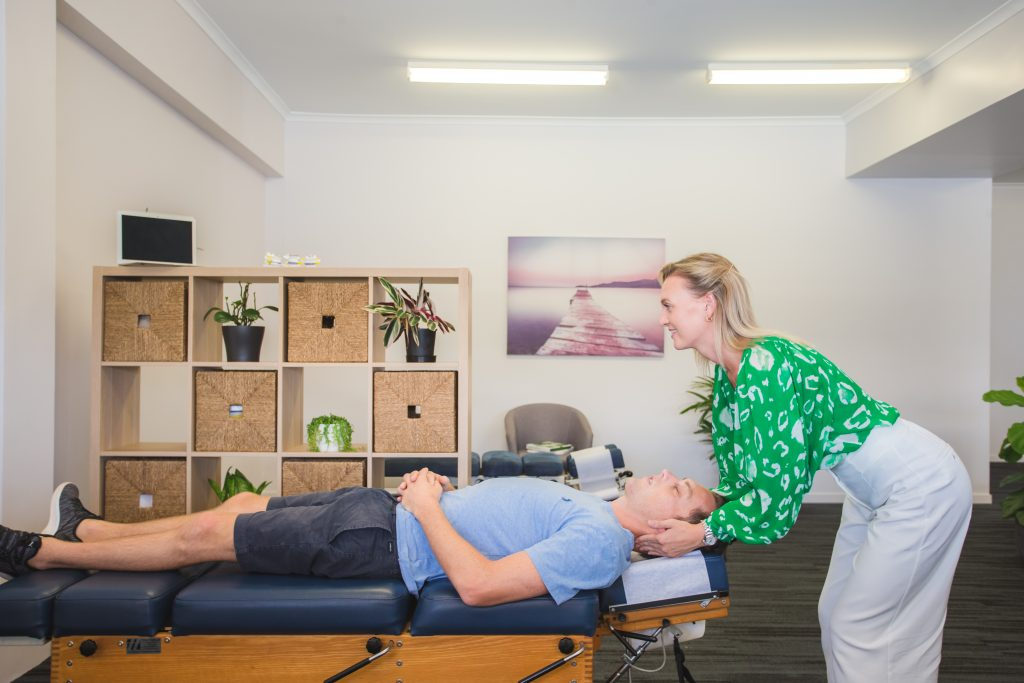 Meikleville Hill Chiropractor performing neck adjustment on male patient