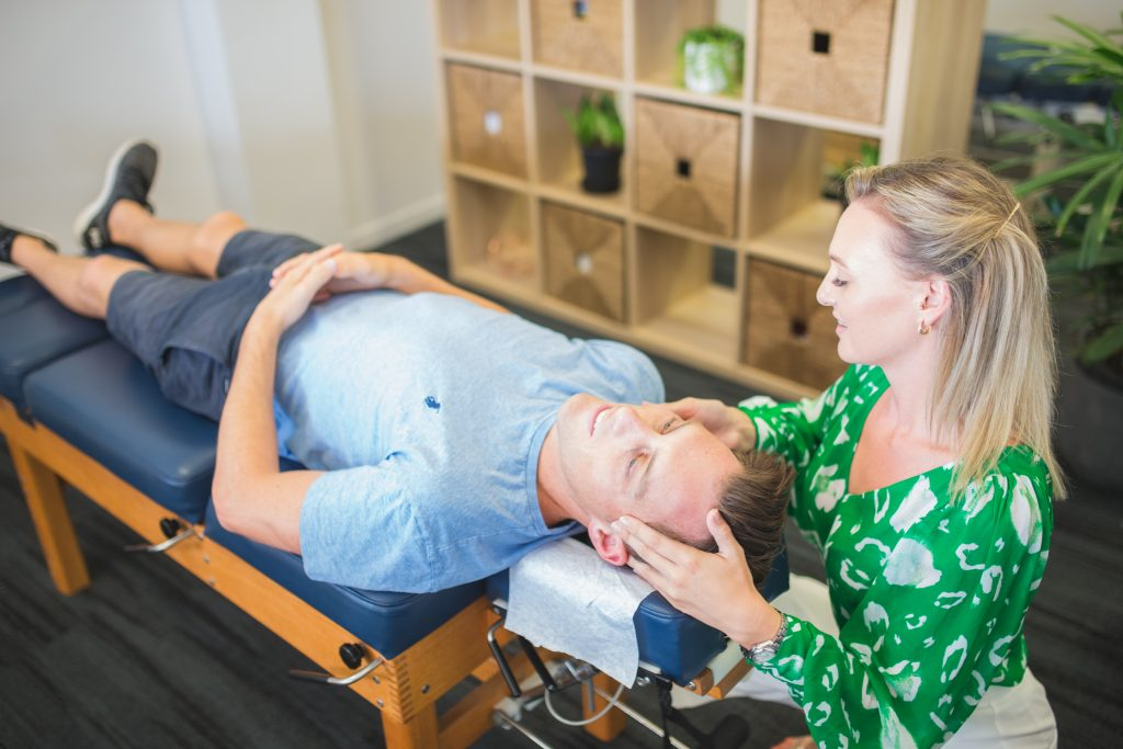 Kinka Beach Chiropractor performing neck adjustment on male patient