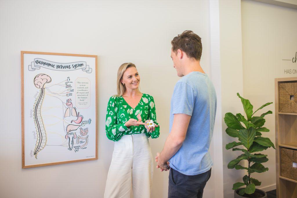 Zilzie Chiropractor talking with male patient using a spinal vertebrae prop