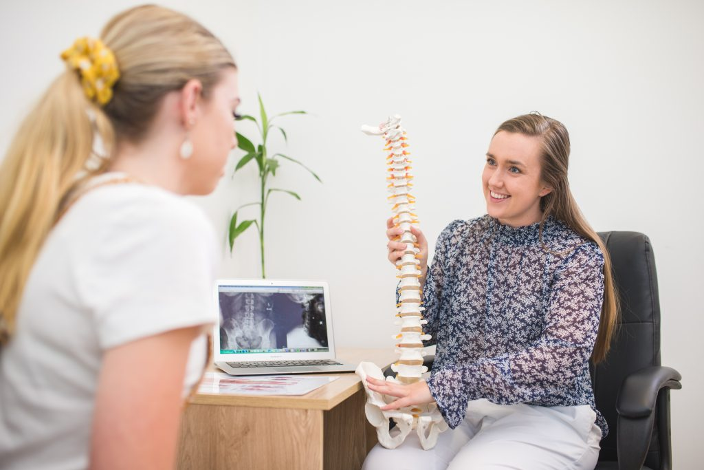 Lammermoor Chiropractor talking with female patient using a spinal prop