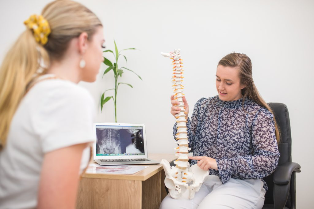 Taroomball Chiropractor talking with female patient, using a spinal prop as a reference point